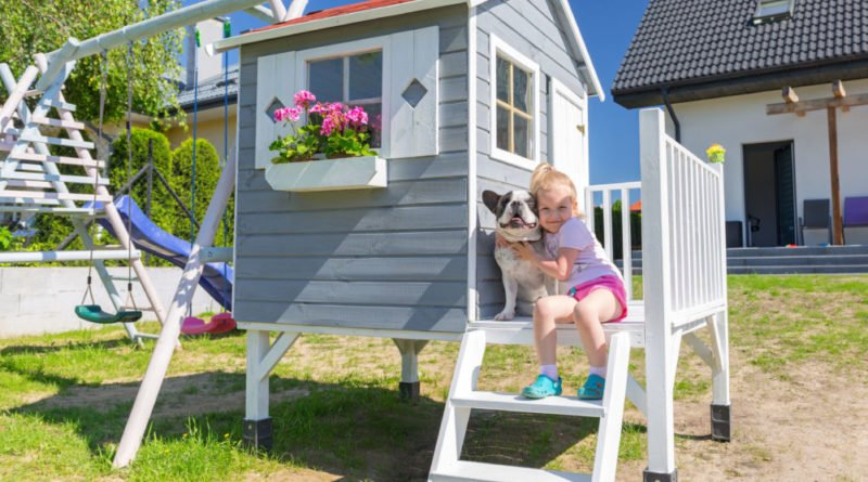 little gril in a playhouse with a dog