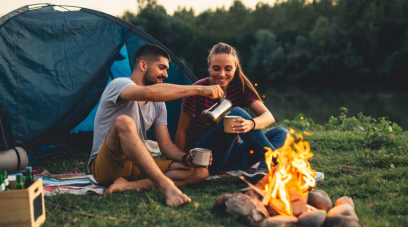 couple camping, drinking coffee by the fire